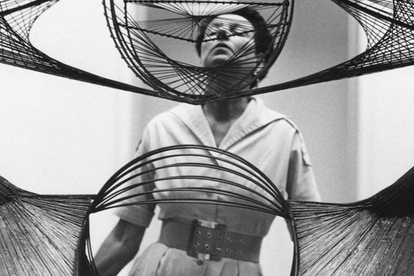 """Peggy Guggenheim seen through a sculpture, from """"Peggy Guggenheim - Art Addict."""" (photo: Roloff Beny)"""